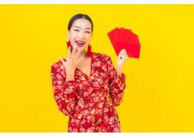 黄色墙上挂着红包的美丽亚洲年轻女子肖像_1204509201
