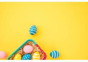 黄色桌子上的小篮子里装着五颜六色的复活节_381074001
