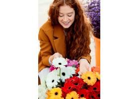 春天带着一束鲜花在户外高角度微笑的女人_1239681601
