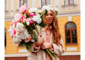 春天时髦的女人手持一束鲜花在户外_1215196701