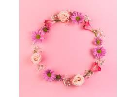 粉红色背景上有鲜花的空白圆形框架_388244601