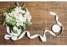 白丝带和花束在木桌上方的盘子上有结婚戒_493713301