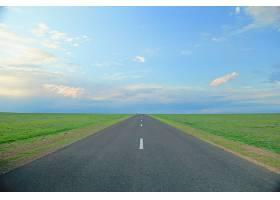 蓝天下被草地包围的道路_1099038701