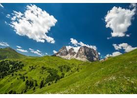 蓝天下远处长满青草的小山和山脉_965574201