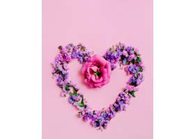 粉色背景上用薰衣草和粉红色花朵制成的心形_257298301