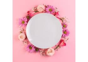 粉色背景上装饰着五颜六色鲜花的白色空盘子_388246001