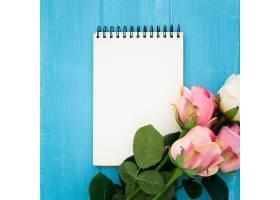 蓝色木头上有笔记本和玫瑰花的漂亮构图_582489201