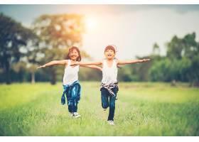 两个可爱的小女孩正在绿色的草地上奔跑最_288728801