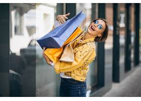城市里提着购物袋的年轻女子_557876601