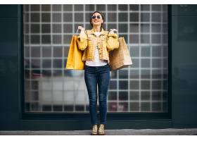 城市里提着购物袋的年轻女子_557878701