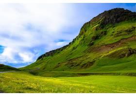 多云天空下一座长满草的山附近长满草的田野_1086133801