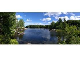多云的天空下绿树环绕的湖泊的美丽景色_1106259801