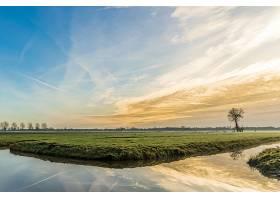 宽阔的草地上水体倒映着美丽的日落和天空_997170201