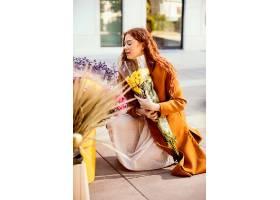 女人在户外采摘春花的侧观_1239684801