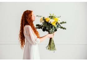 女人拿着一束美丽的春花摆姿势的侧观_1239683501
