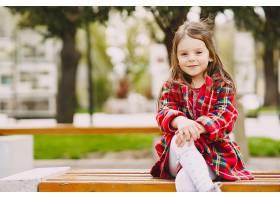 公园里的小女孩坐在长凳上_889808001