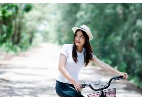 公园里骑自行车的年轻美女的肖像_501707801