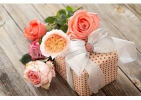 包装精美的礼物和一束玫瑰花放在一张模糊的_1192486901