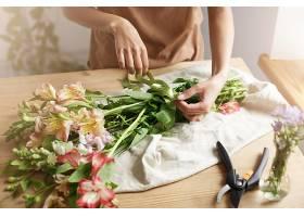 工作场所年轻的女花商在花束上系丝带的特写_881184801