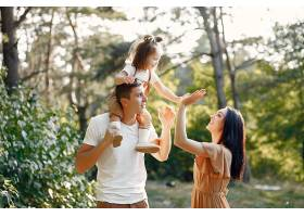 可爱的一家人在秋天的田野里玩耍_716974401