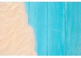 带复制空间的蓝色木质背景上的沙边_450052101