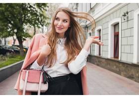 可爱迷人时尚微笑的女人穿着粉色外套走在城_1027220501