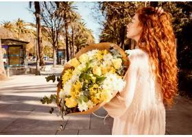 带着一束春花的女人在户外侧观_1239681701