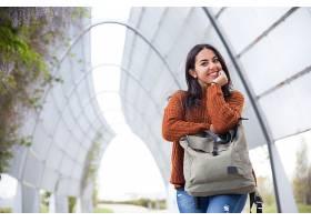 城市公园里靠在手提包上的快乐年轻女子_453018201