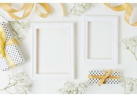 金丝带礼品盒白色背景的木框附近有婴儿_493718201