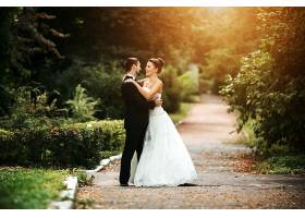 微笑的新婚夫妇在日落时摆姿势_98356601