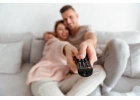 微笑着相爱的夫妇一起坐在沙发上看电视关_651197101