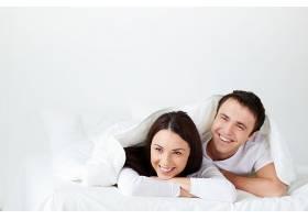 一对夫妇在床上大笑_86711401