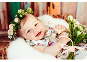 小女孩躺在篮子里的膝盖上放着一束小玫瑰_112059101