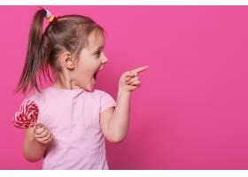 小孩子张大嘴巴兴奋地看着另一边手里拿_876099101