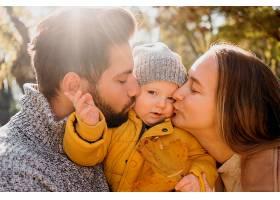 爸爸和妈妈在外面抱着孩子的侧视_1190465501