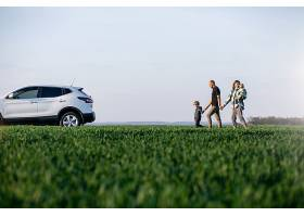 带着孩子开车旅行的年轻家庭在田野里停了_838051301