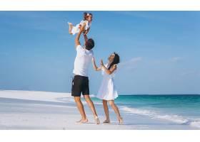 带着小女儿的年轻家庭在海边度假_517576501