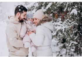带着小女儿的年轻家庭在满是白雪的冬日森林_664164101
