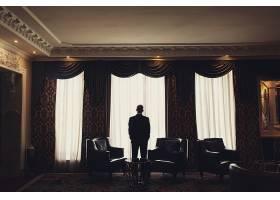 一个孤独的人站在房间的窗户前_127520901