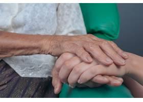 一位年轻女子牵着一位老妇人的手_483533101
