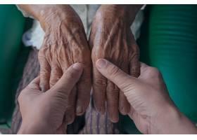一位年轻女子牵着一位老妇人的手_483533201