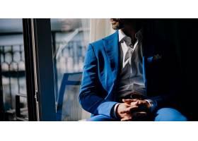 一位穿着蓝色西装的深思熟虑的男子坐在窗台_398306301