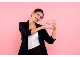 身穿深色夹克的前视年轻女性在粉色背景上展_1254776301