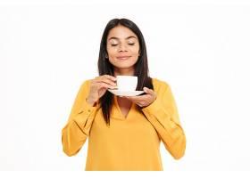 一位可爱的年轻女子闻着茶杯的肖像_728670201