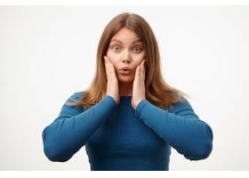 一位年轻可爱的长发女子身着蓝色上衣站在白_1258587401