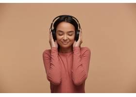 一位年轻女子戴着黑色大耳机听她最喜欢的音_1026880601