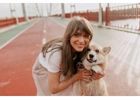 一位棕色头发的可爱女人带着她的狗在早晨的_1082162701