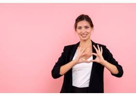 前视穿深色夹克的年轻女性在粉色背景上示爱_1254776101