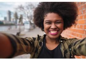年轻漂亮的美国黑人女子在街上户外自拍的肖_1044919201