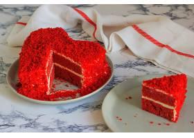 心形红色天鹅绒蛋糕放在大理石桌上切成薄_543010901